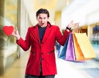 Glimlachende knappe mensenholding het winkelen zakken en rood hart Royalty-vrije Stock Foto's