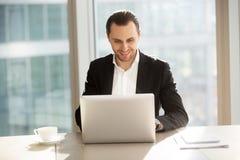 Glimlachende knappe zakenman die aan laptop in bureau werken Royalty-vrije Stock Foto