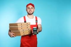Glimlachende koerier met pizzadozen en betalingsterminal op kleurenachtergrond stock afbeelding