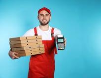 Glimlachende koerier met pizzadozen en betalingsterminal op kleurenachtergrond stock foto's