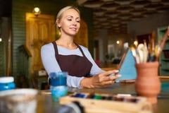 Glimlachende Kunstenaar Looking bij haar die schilderen royalty-vrije stock afbeeldingen