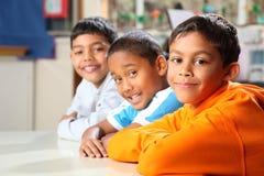 Glimlachende lage schoolvrienden samen in klasse Stock Afbeeldingen