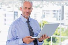 Glimlachende laptop van de zakenmanholding Stock Foto's