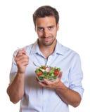 Glimlachende Latijnse mens die salade eten Royalty-vrije Stock Afbeelding