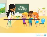 Glimlachende leraar en kinderen die door vergrootglas naar groene spruit tijdens biologieles kijken in klaslokaal Stock Foto's