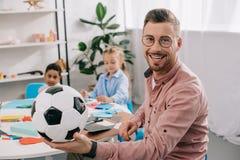 glimlachende leraar met voetbal erachter bal en multiculturele klasgenoten royalty-vrije stock foto