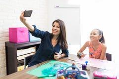 Glimlachende Leraar And Student Drawing terwijl thuis het Spreken van Selfie stock afbeelding