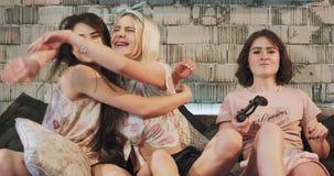 Glimlachende leuke drie dames die een goede tijd doorbrengen die samen in een PlayStation-spel voor de zeer grappige camera spele stock footage