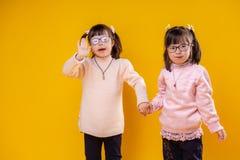 Glimlachende leuke meisjes met chromosoomabnormaliteit die samen blijven stock fotografie