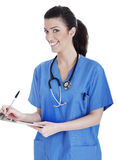 Glimlachende leuke verpleegster die haar medische nota's maakt Stock Foto