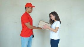 Glimlachende leveringsman die pakket leveren aan een vrouw stock video