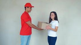 Glimlachende leveringsman die pakket leveren aan een vrouw stock footage
