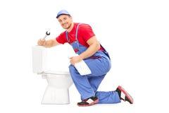 Glimlachende loodgieter die een toilet proberen te bevestigen Stock Foto's