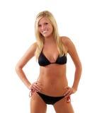 Glimlachende magere jonge blonde vrouw in zwarte bikini Royalty-vrije Stock Foto