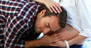 Glimlachende man die aan de buik van de zwangere vrouw in afdeling luisteren stock footage