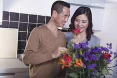 Glimlachende man roze houden en vrouw die het ruiken voor een kleurrijk boeket van bloemen in de keuken Stock Afbeeldingen