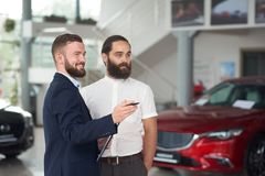 Glimlachende manager die aan klantenauto's tonen royalty-vrije stock afbeelding