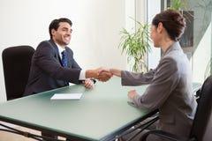 Glimlachende manager die een knappe kandidaat interviewt royalty-vrije stock foto's