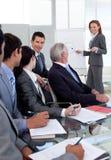 Glimlachende manager die een presentatie geeft aan haar team stock afbeelding