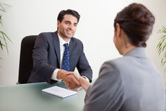 Glimlachende manager die een vrouwelijke kandidaat interviewt stock afbeeldingen