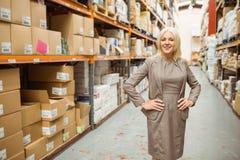 Glimlachende manager die haar handen plaatsen op haar heupen stock foto's