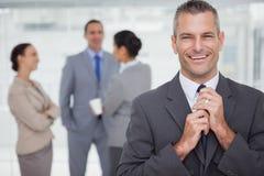 Glimlachende manager die zijn band met werknemers op achtergrond opruimen royalty-vrije stock afbeelding
