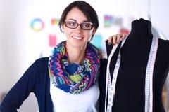 Glimlachende manierontwerper die zich dichtbij ledenpop in bureau bevinden Stock Afbeeldingen