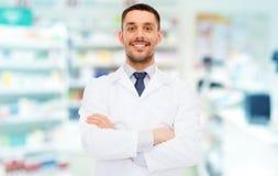 Glimlachende mannelijke apotheker in witte laag bij drogisterij Stock Afbeeldingen