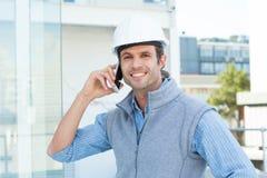 Glimlachende mannelijke architect die mobiele telefoon in openlucht met behulp van Royalty-vrije Stock Foto
