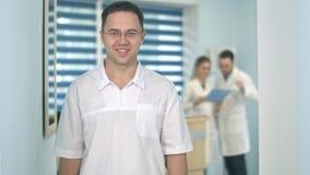 Glimlachende mannelijke arts die in glazen camera bekijken terwijl medisch personeel die aan de achtergrond werken Stock Fotografie