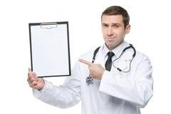Glimlachende mannelijke arts die vinger richten aan klembord Stock Afbeelding