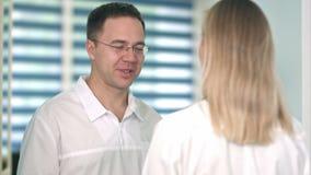 Glimlachende mannelijke arts in glazen die aan vrouwelijke verpleegster spreken stock footage