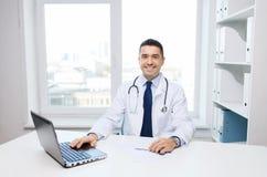Glimlachende mannelijke arts met laptop in medisch bureau Royalty-vrije Stock Foto