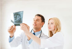 Glimlachende mannelijke arts of tandarts die röntgenstraal bekijken Royalty-vrije Stock Foto