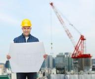 Glimlachende mannelijke bouwer in helm met blauwdruk Stock Fotografie