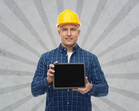 Glimlachende mannelijke bouwer in helm met tabletpc Stock Foto