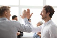 Glimlachende mannelijke collega's die hoogte vijf in bureau geven die v vieren stock afbeeldingen