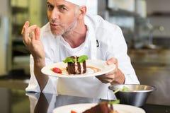 Glimlachende mannelijke gebakjechef-kok met dessert in keuken Stock Afbeeldingen