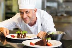 Glimlachende mannelijke gebakjechef-kok met dessert in keuken Stock Foto