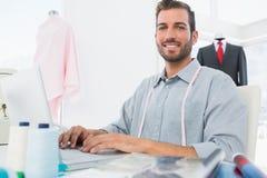 Glimlachende mannelijke manierontwerper die laptop in studio met behulp van Royalty-vrije Stock Foto's