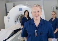Glimlachende Mannelijke Radioloog With Colleagues Standing door MRI-Machine Stock Foto's