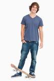 Glimlachende mannelijke student met een skateboard stock fotografie