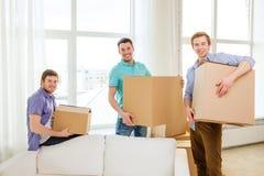 Glimlachende mannelijke vrienden die dozen dragen op nieuwe plaats stock afbeelding
