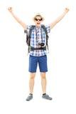 Glimlachende mannelijke wandelaar met opgeheven handen die geluk gesturing Royalty-vrije Stock Afbeeldingen