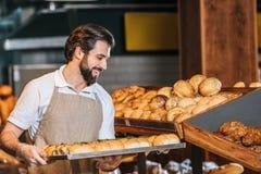 glimlachende mannelijke winkelmedewerker die vers gebakje schikken royalty-vrije stock afbeeldingen
