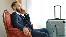 Glimlachende mannelijke zakenman die met partner spreken die smartphone gebruiken tijdens zakenreis stock video