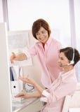 Glimlachende medewerkers die het werk in bureau bespreken Royalty-vrije Stock Foto