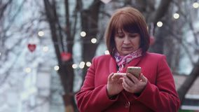 Glimlachende medio volwassen vrouw die smartphone het ontspannen in park gebruiken Lichten op achtergrond stock video