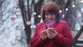 Glimlachende medio volwassen vrouw die smartphone het ontspannen in park gebruiken Lichten op achtergrond Langzame Motie stock footage