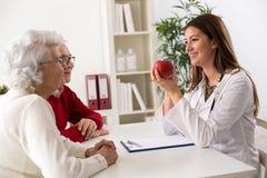 Glimlachende medische artsenvrouw die appel aanbieden aan hoger paar stock afbeelding